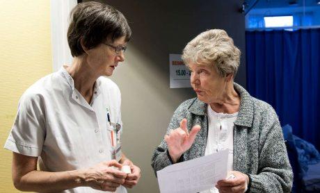 Sygeplejersker taler med patient . DSR er medlem af Fagbevægelsens Hovedorganisation