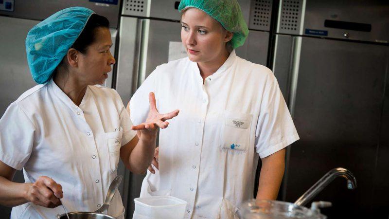 To køkkenassistenter drøftter arbejdet