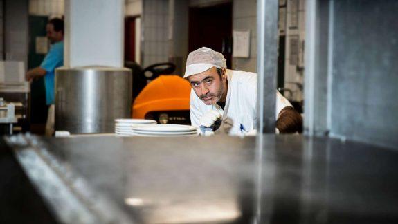kækkenassistent kigger langt ind i ovnen
