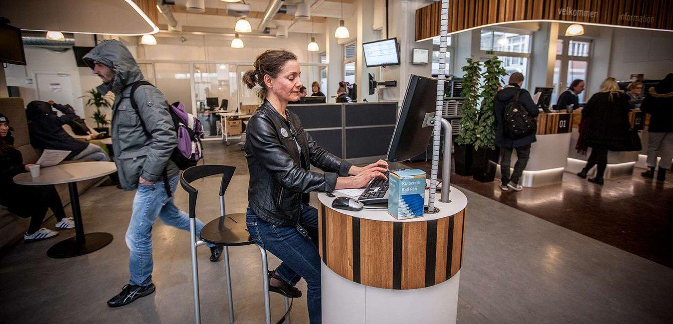Kvinde skriver ansøgning i et jobcenter