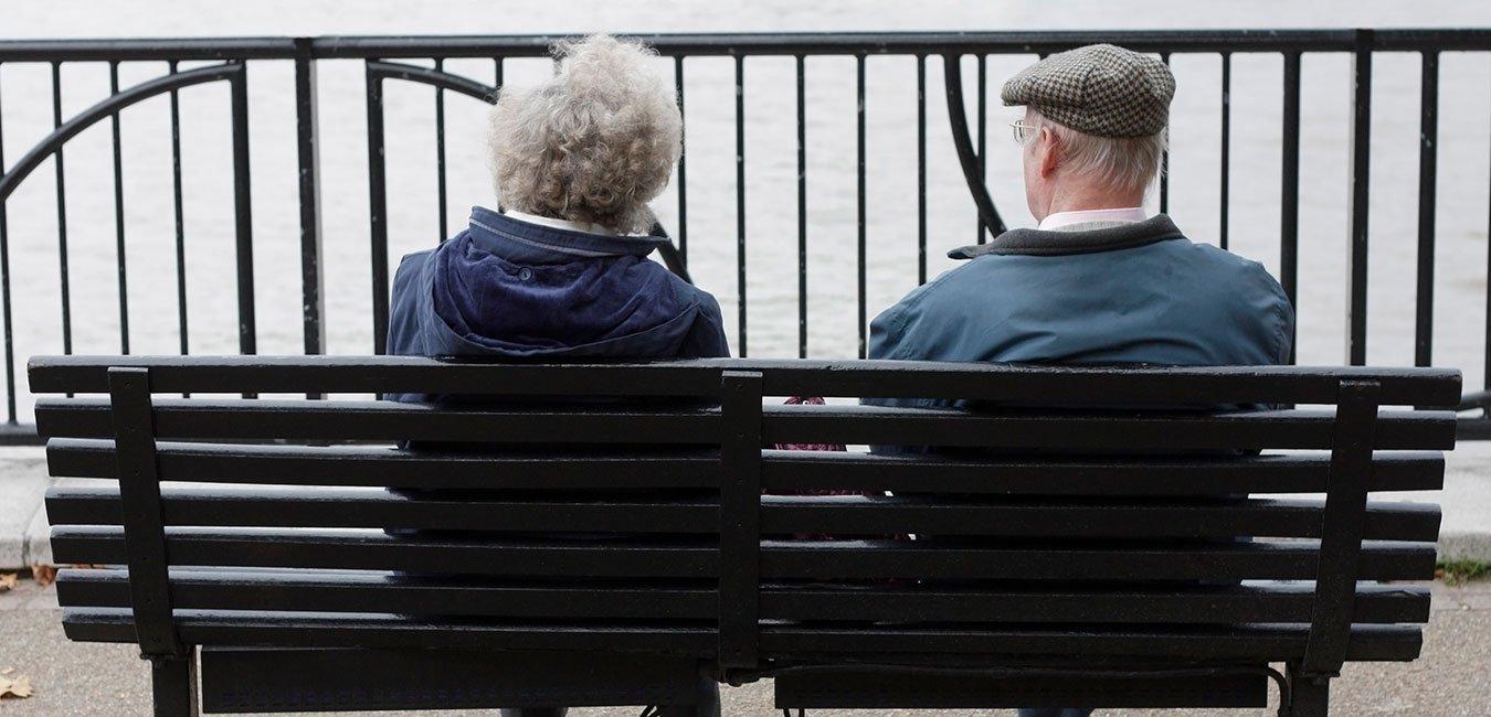 Ældre ægtepar sidder på en bænk og kigger ud over vandete