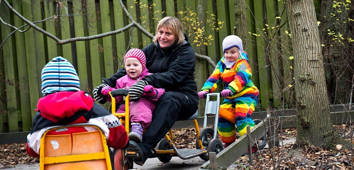 Pædagog og børn kører i vogn på legepladsen. Fagbevægelsens Hovedorganisation