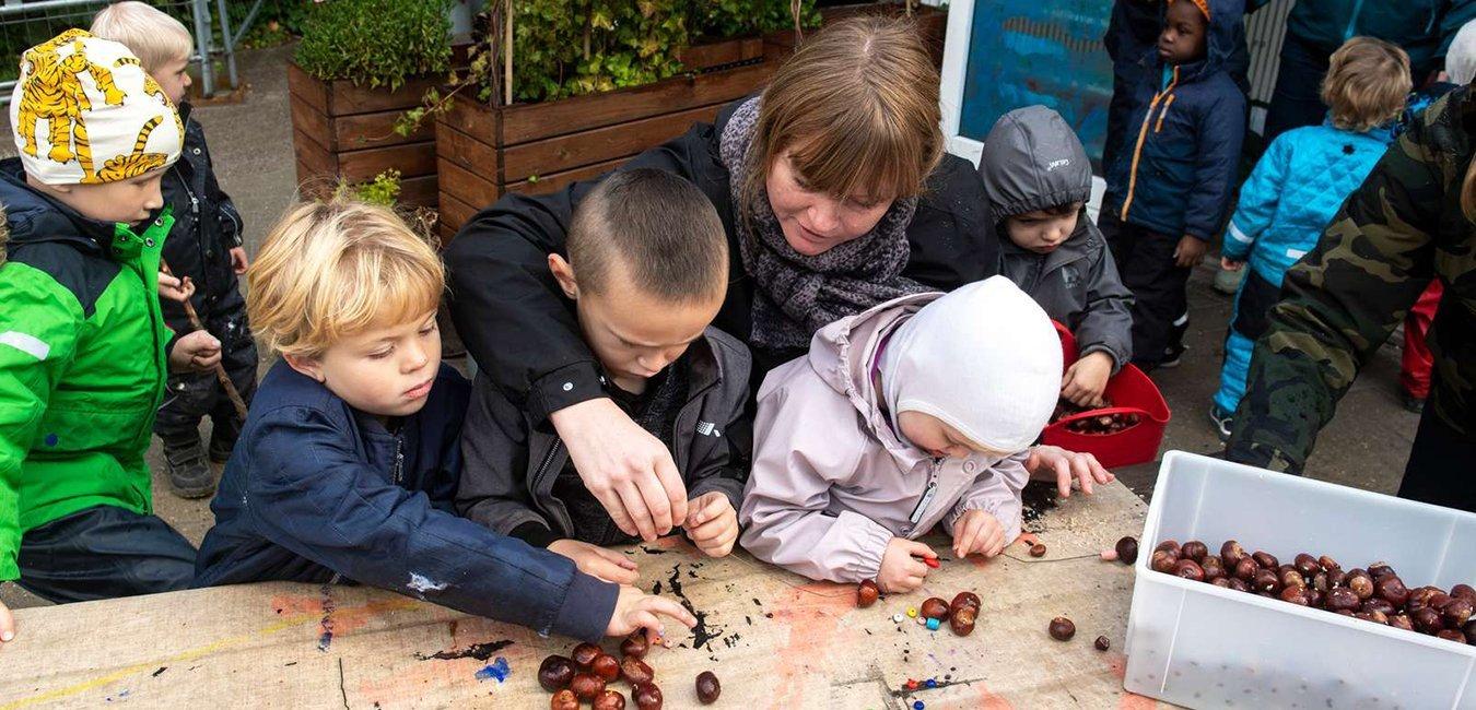 Pædagog sidder uden for og laver kastanjer med børnene. Fagbevægelsens Hovedorganisation