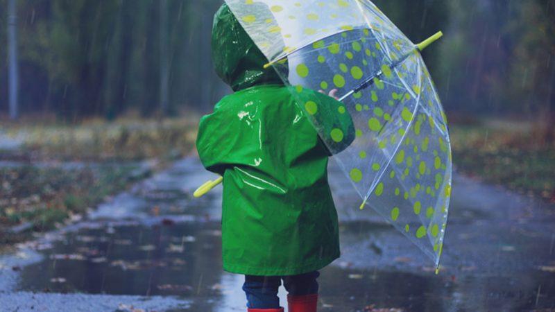 Klime, lille barn i grøn rækkefrakke med gennemsigtig paraply