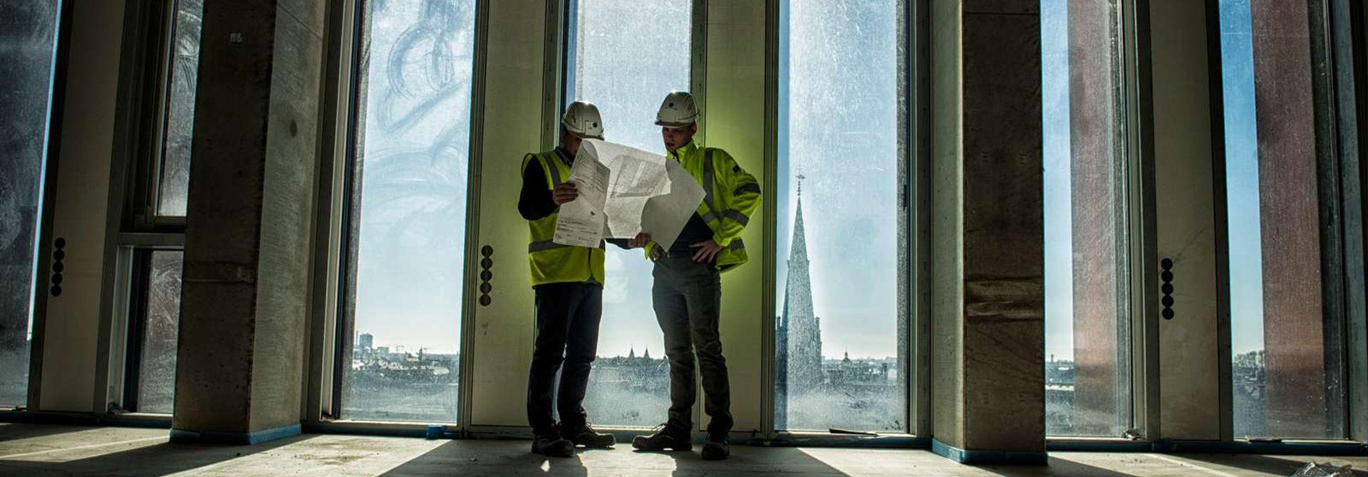 Fagbevægelsens Hovedorganisation, 2 byggekonstruktører kigger på tegninger sammen på byggeplads højt oppe med flot klar udsigt, Ludvigsen