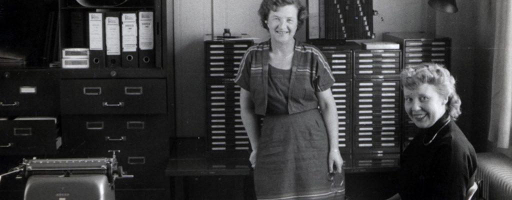 Fagbevægelsens Historie: FTF Dannes. To glade kvinder på et kontor. 1950'erne. Op gennem 50'ern og 60'erne bliver der flere og flere funktionærer på arbejdsmarkedet. Danmark er ikke længere hovedsageligt et industri- og landbrugssamfund; arbejdet er i stor stil ved at rykke fra industrien til skrivebordet.